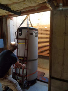 Guiding the heater as it is lowered into the utility basement.